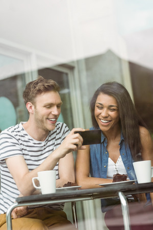 college student: Smiling friends with chocolate cake using smartphone in cafe at the university Stock Photo