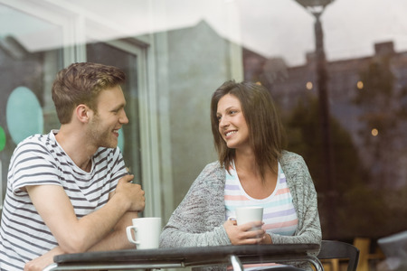 lifestyle caucasian: Smiling friends with mug of coffee in cafe at the university