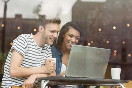 internet cafe: Amigos sonrientes con una bebida caliente utilizando el port�til en caf� en la universidad
