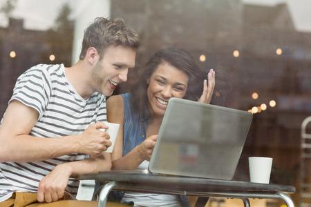 usando computadora: Amigos sonrientes con una bebida caliente utilizando el portátil en café en la universidad