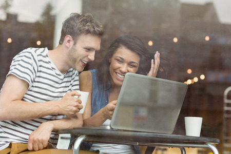 Smiling friends with a hot drink using laptop in cafe at the university