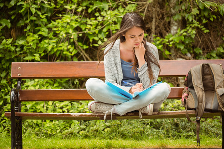outdoor bench: Smiling student sitting on bench reading book in park at school Stock Photo
