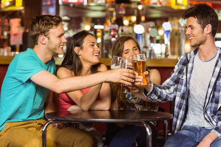 pub: Portrait of happy friends toasting with drink and beer in a pub