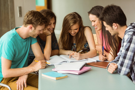 estudiando: Amigos sonriente sentado estudiando juntos despu�s de la escuela