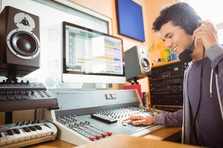 Portrait of an university student mixing audio in a studio of a radio 스톡 콘텐츠