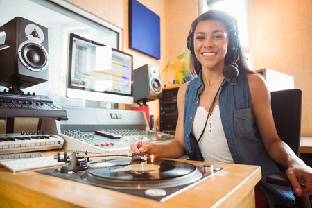 Portrait of an university student with a turn table in the studio of a radio