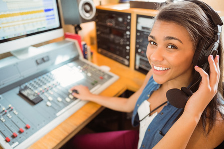 Smiling university student mixing audio in the studio of a radio