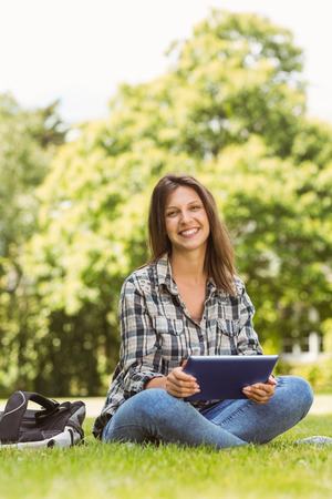 scrolling: Smiling student sitting and using tablet pc in park at school Stock Photo