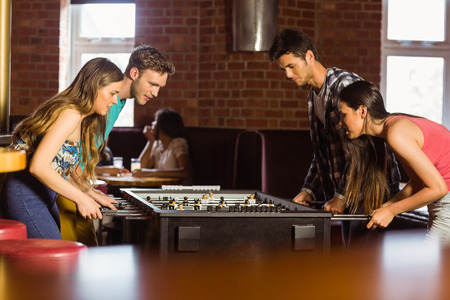 sports bar: Smiling friends playing table football in a pub