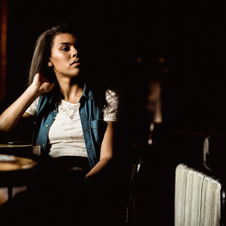 lonesomeness: Pretty student sitting alone and thinking in a pub