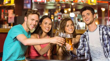 jovenes tomando alcohol: Retrato de amigos felices brindando con bebidas y cerveza en un pub