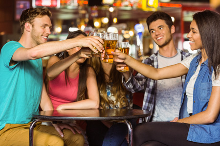 Gelukkige vrienden roosteren met drank en bier in een pub