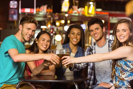 Portret van gelukkige vrienden roosteren met drankje en bier in een pub