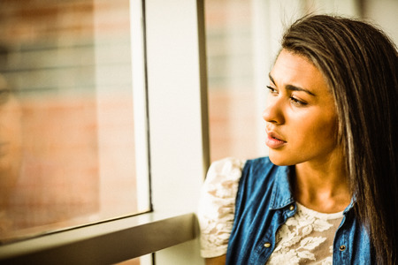 solitariness: Pretty brunette sitting alone unsmiling against a window
