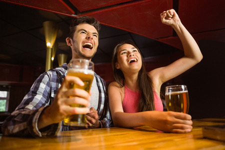 sports bar: Happy friends drinking beer and cheering together in a bar
