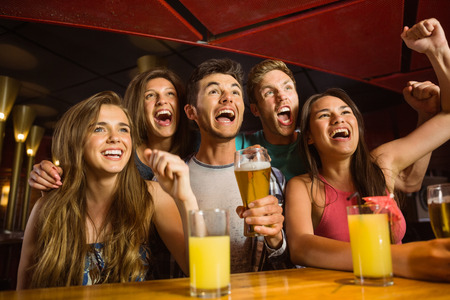 barra: Amigos felices bebiendo cerveza y aplaudir juntos en un bar