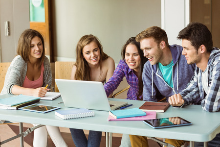 college student: Smiling friends students using laptop at school