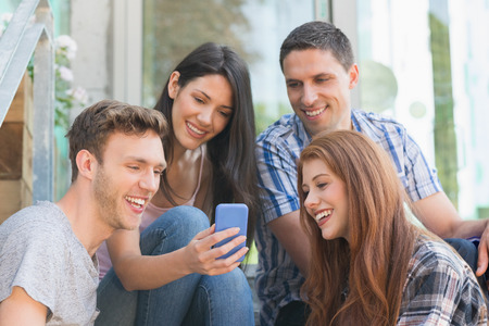 college student: Happy students looking at smartphone outside on campus at the university
