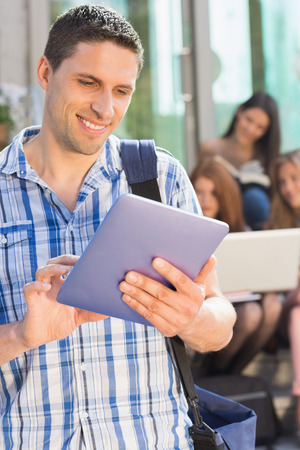 Happy student using his tablet pc on campus at the university photo