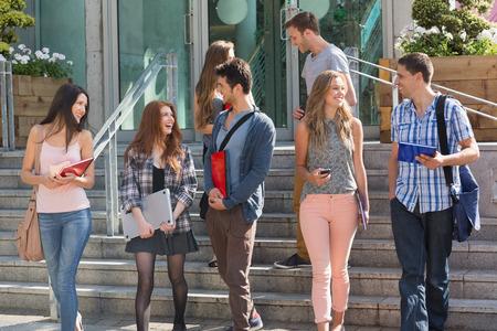 colegios: Estudiantes felices caminando y charlando fuera en la universidad Foto de archivo