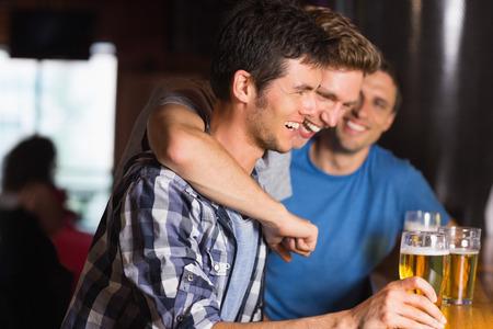 barra: Amigos felices que cogen a lo largo de pintas en un bar