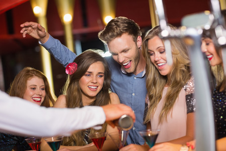 ebrio: Amigos borrachos viendo camarero c�ctel verter en el club nocturno