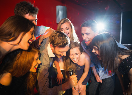 gente cantando: Amigos felices cantando karaoke juntos en un bar Foto de archivo