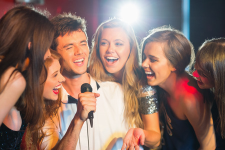 canto: Amigos felices cantando karaoke juntos en un bar Foto de archivo