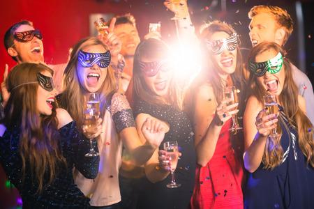 borracho: Amigos en las máscaras de disfraces beber champán en la discoteca