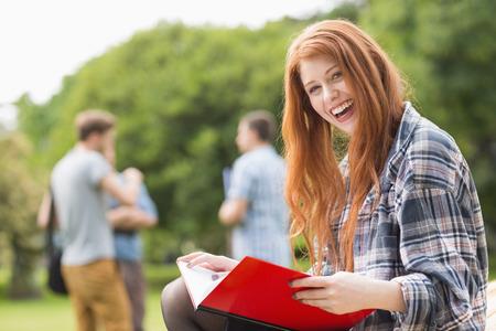 estudiantes universitarios: Pretty estudiante estudiando fuera en el campus de la universidad Foto de archivo