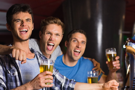 excited man: Happy friends catching up over pints in a bar