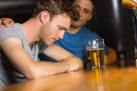 Caring friend comforting upset man in a bar
