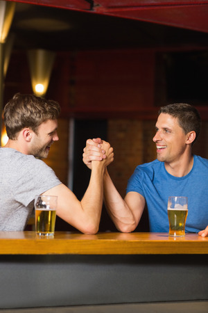 wrestle: Happy friend arm wrestling each other in a bar