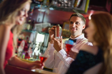 shaking out: Handsome barman chatting to customers in a bar