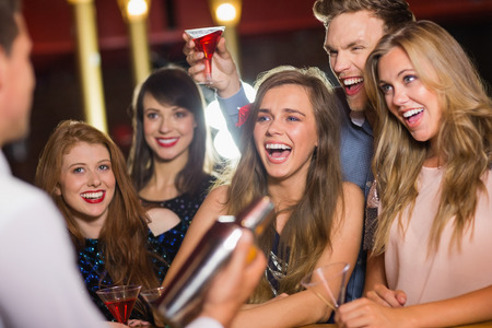 Drunk friends watching barman making cocktail at the nightclub photo