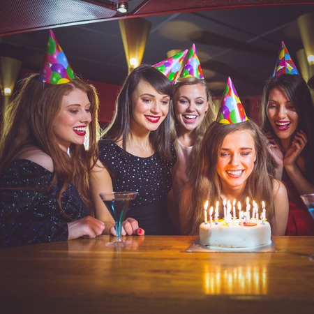 party hat: Friends celebrating a birthday together at the nightclub Stock Photo