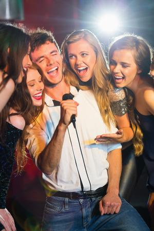 Gl�ckliche Freunde, die Karaoke singen zusammen in einer Bar