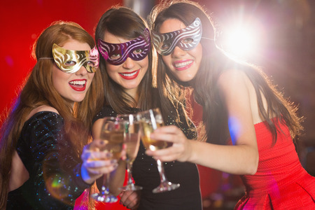 hedonistic: Friends in masquerade masks toasting with champagne at the nightclub Stock Photo