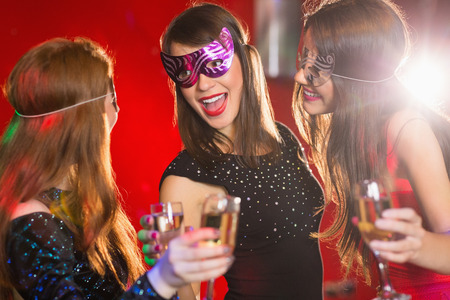 masquerade masks: Friends in masquerade masks drinking champagne at the nightclub