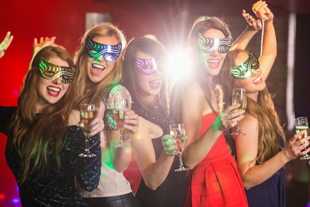 hedonistic: Friends in masquerade masks drinking champagne at the nightclub
