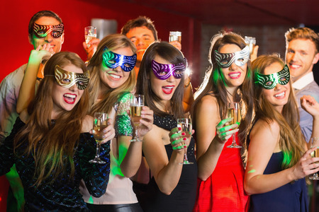 Friends in masquerade masks drinking champagne at the nightclub