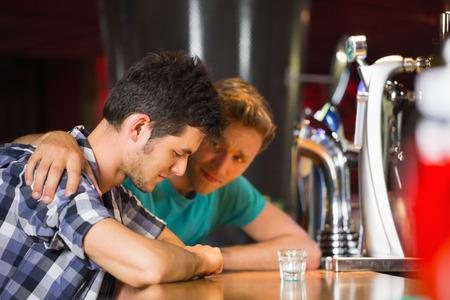 思いやりのある友達慰め動揺バーで男 写真素材