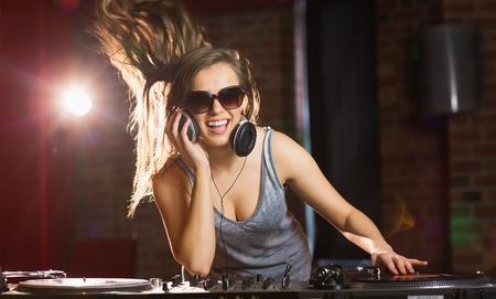 nightclub: Pretty dj smiling and dancing at the nightclub Stock Photo