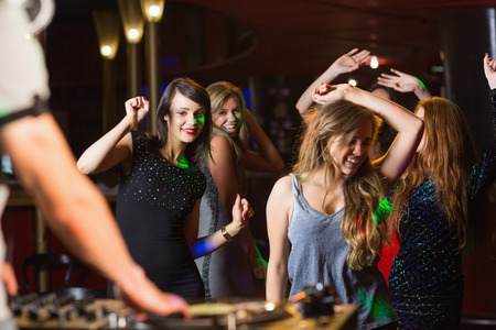 hedonistic: Happy friends dancing by the dj booth at the nightclub
