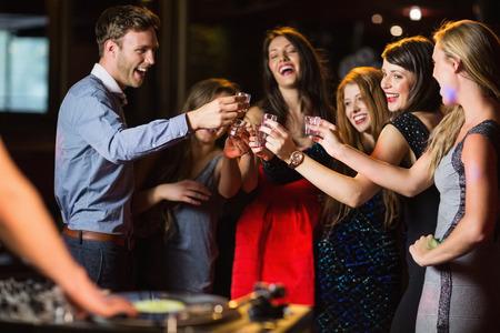 borracho: Amigos felices disparos bebiendo por la cabina del DJ en la discoteca