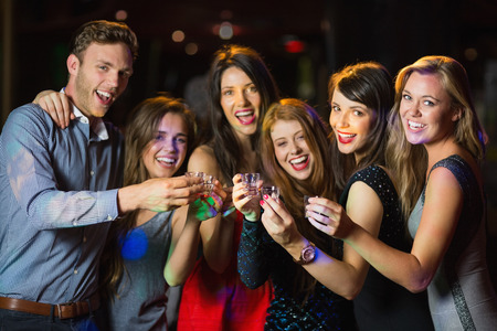 hedonistic: Happy friends drinking shots smiling at camera at the nightclub