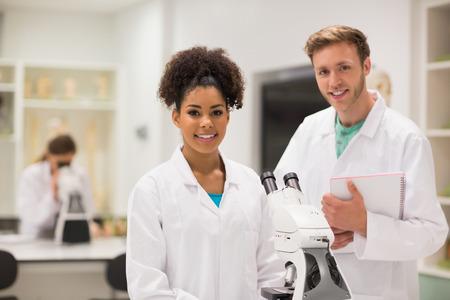 estudiantes medicina: Estudiantes de medicina feliz trabajando con el microscopio en la universidad
