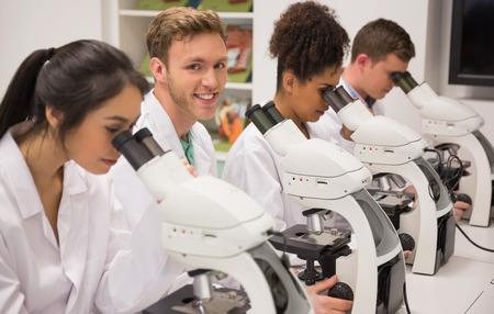 equipos medicos: Los estudiantes de medicina que trabajan con el microscopio en la universidad Foto de archivo
