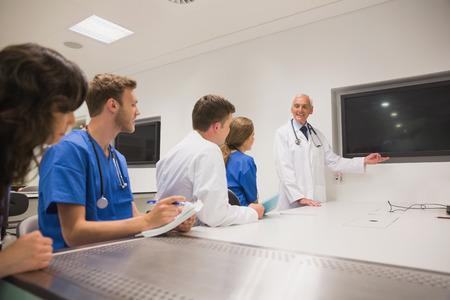 profesora: Profesor de Medicina ense�ar a los j�venes estudiantes en la universidad Foto de archivo