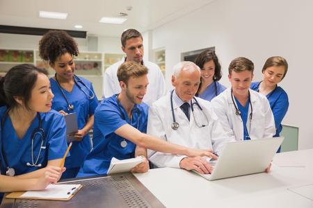 profesor: Estudiantes de medicina y profesor usando la computadora portátil en la universidad